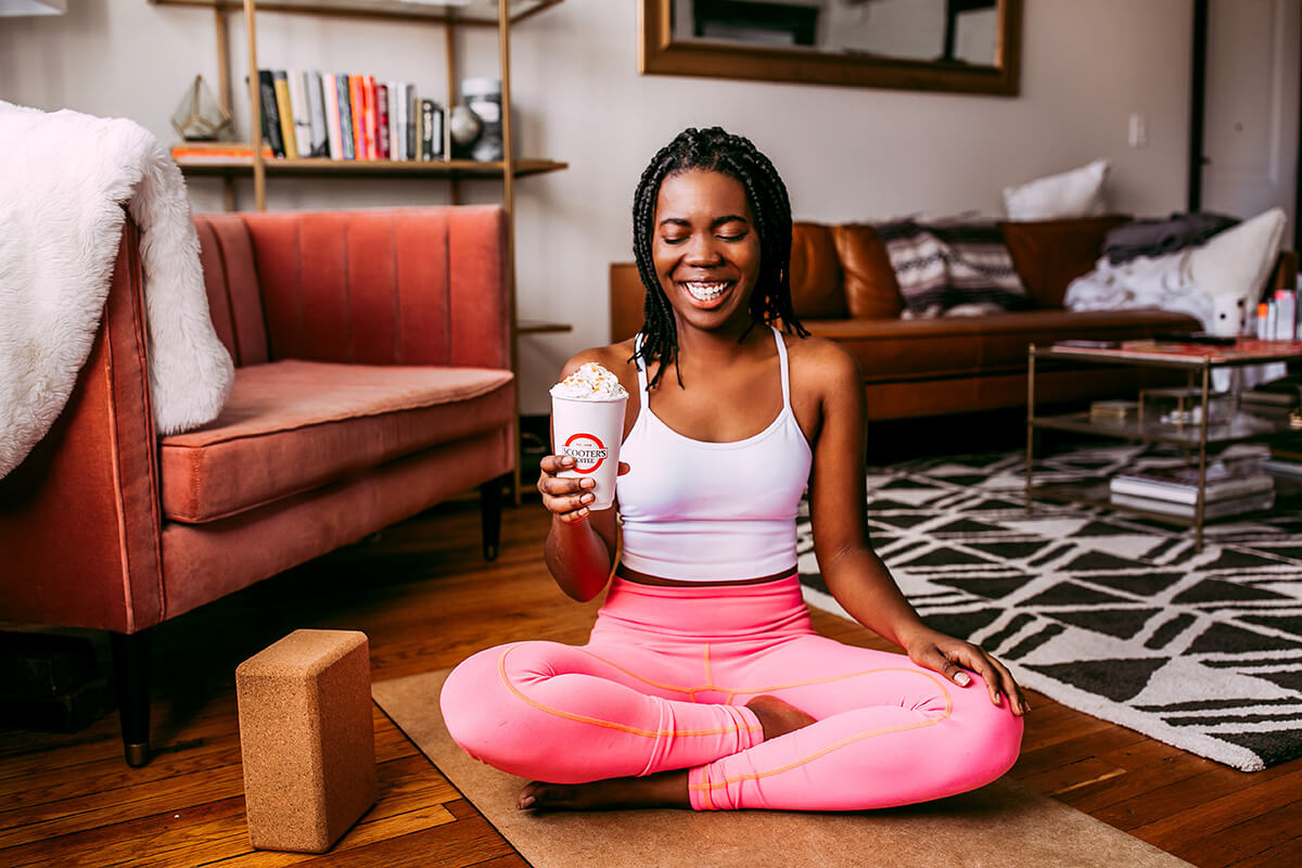 Woman in yoga pose holding coffee