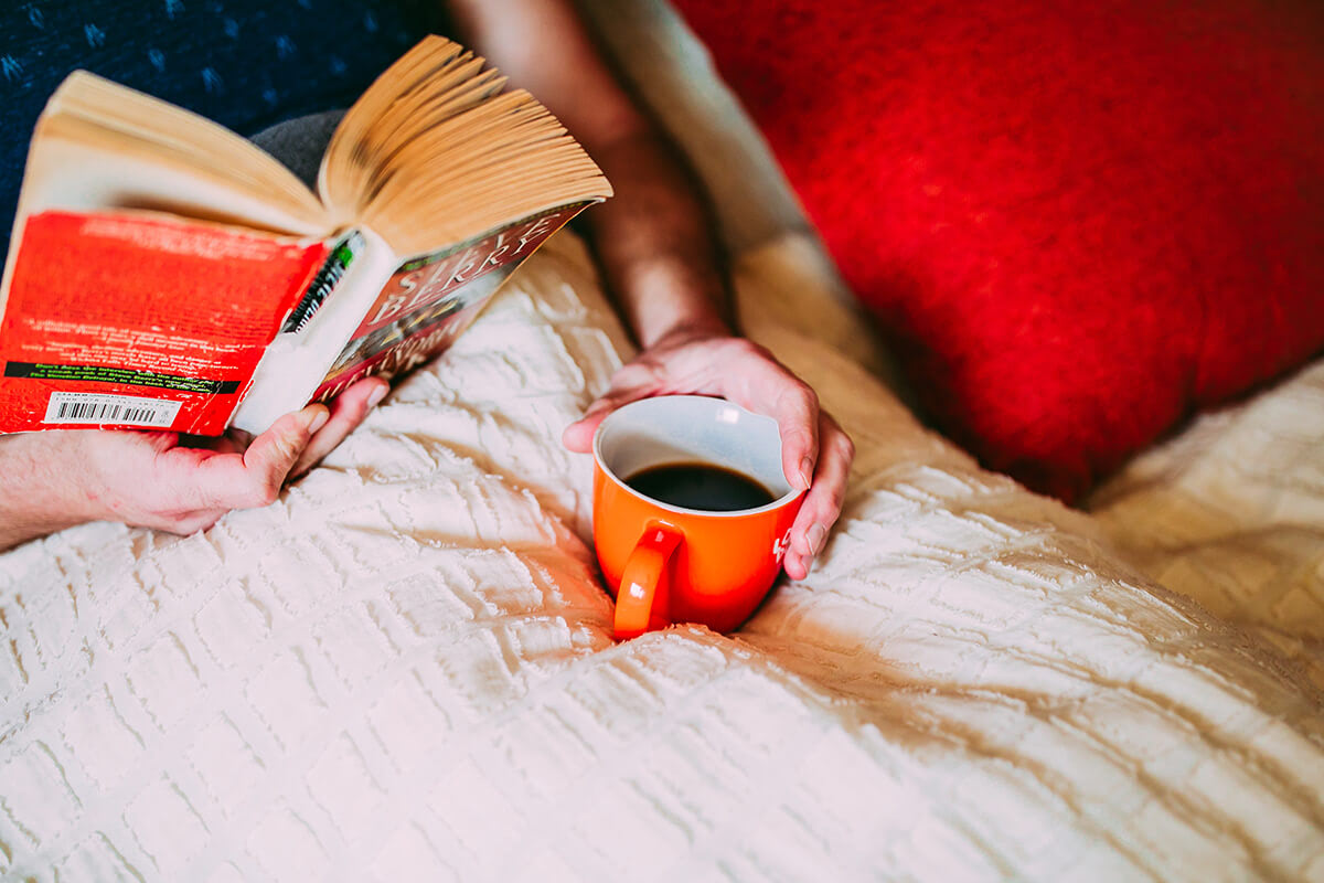 Person sitting in bed with coffee reading a book