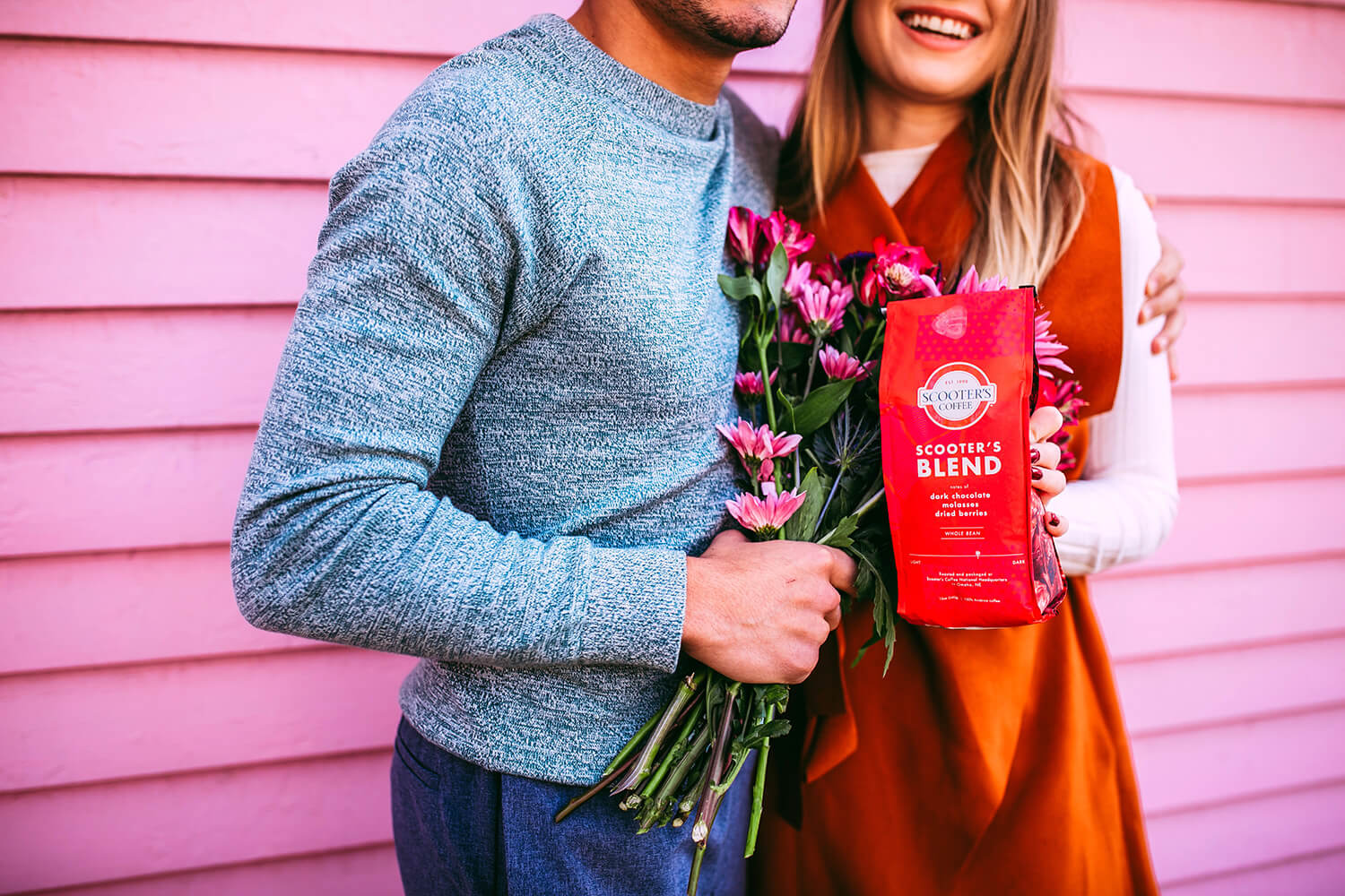 Man holding flowers next to woman holding red Scooter's Coffee bagged coffee