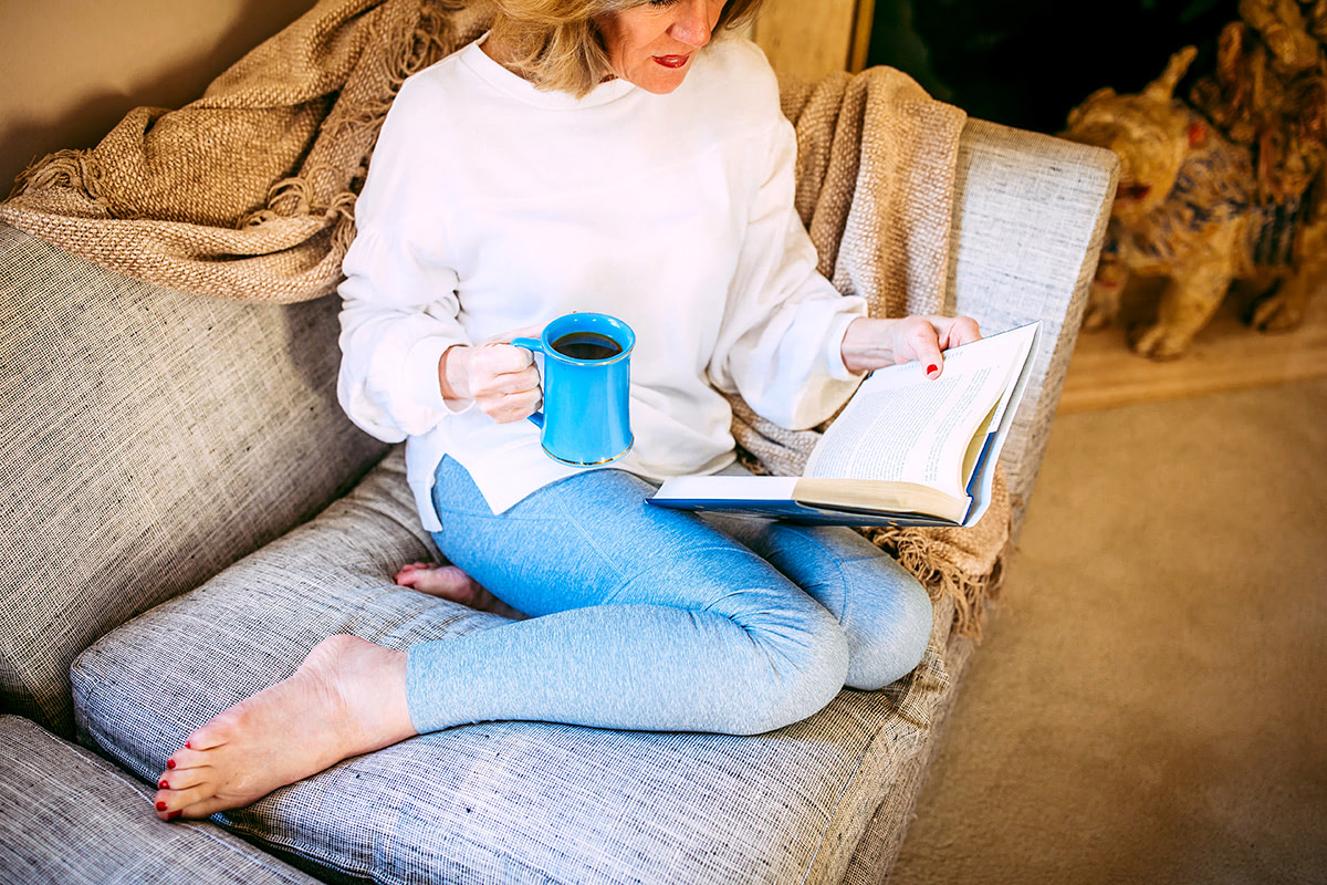 Woman on couch reading book with coffee