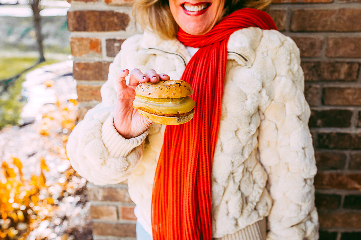 Woman smiling holding breakfast sandwich