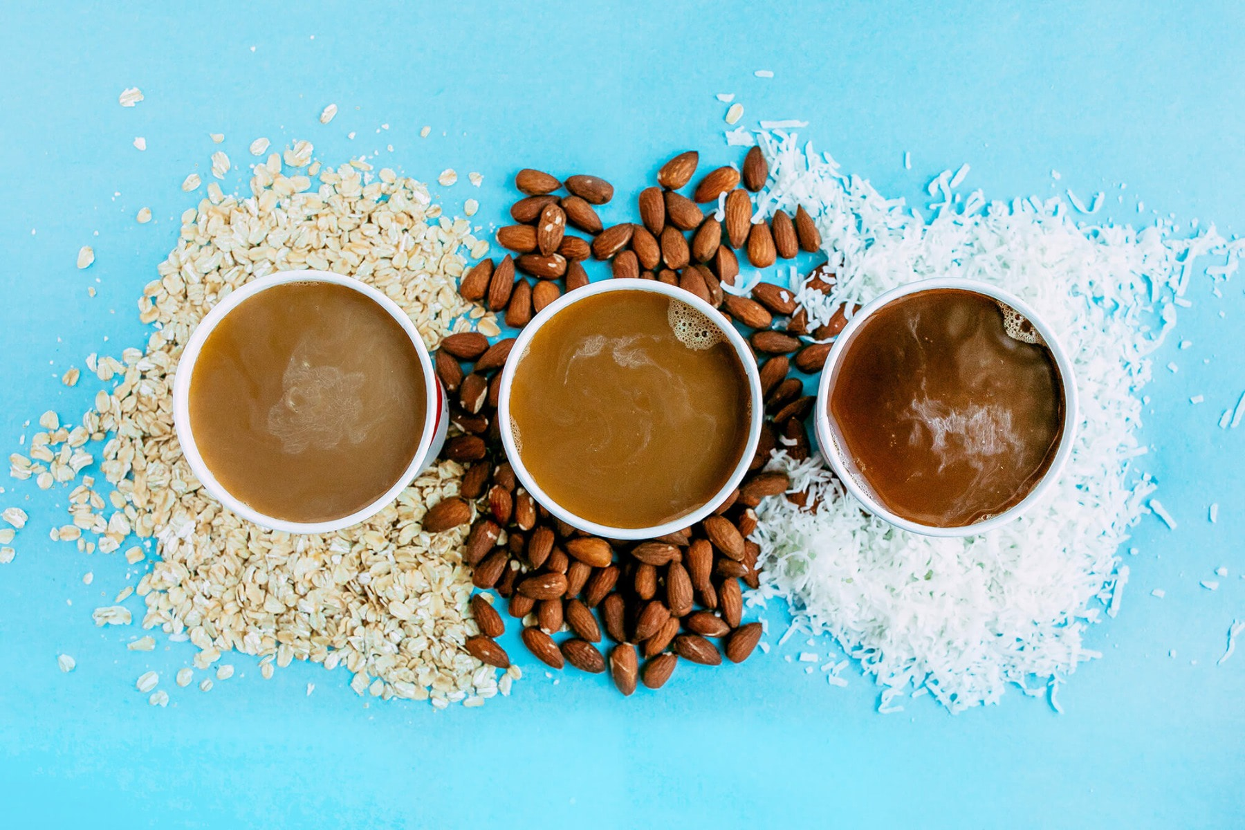 Top shot of three cups of coffee sitting on blue table with oats, almonds and coconut