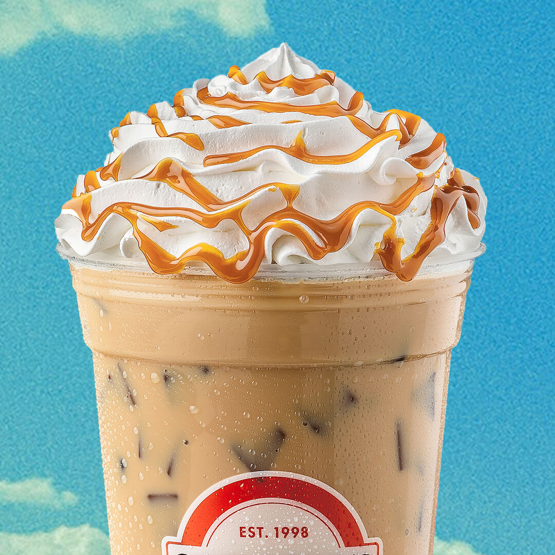 Iced coffee topped with whipped cream and caramel drizzle on blue background