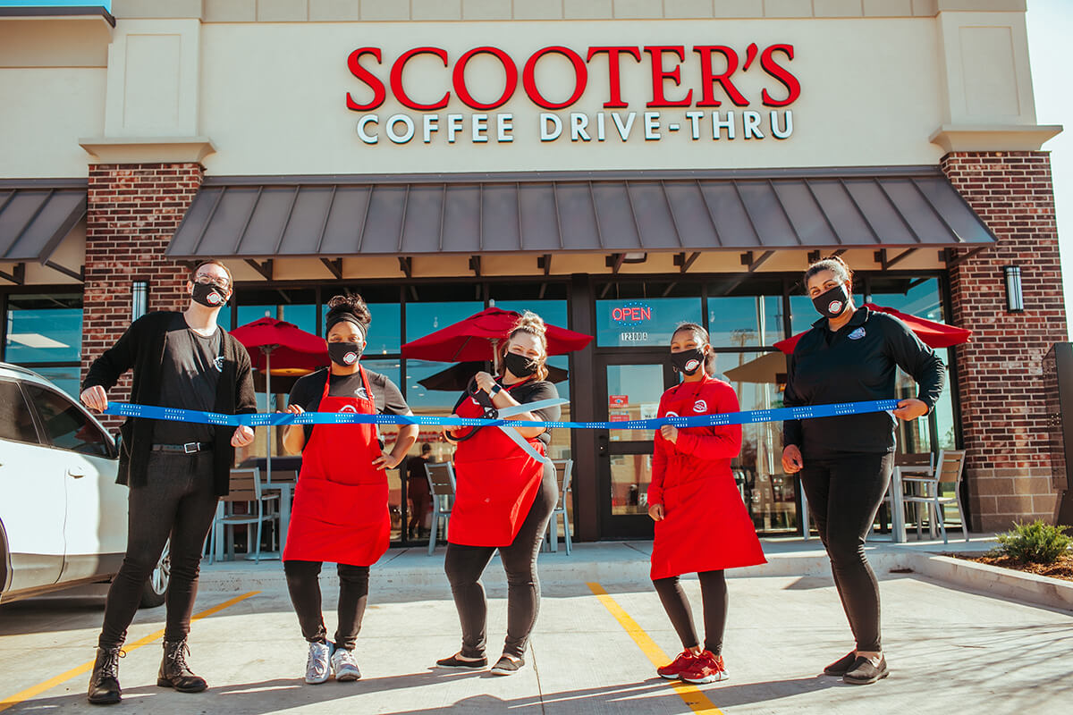 Five people cutting a ribbon standing in front of Scooter's Coffee
