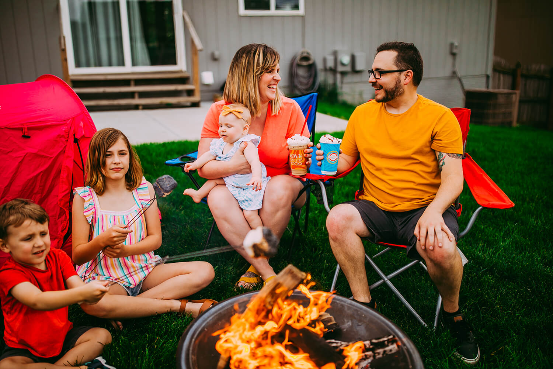 Parents and children in backyard around campfire