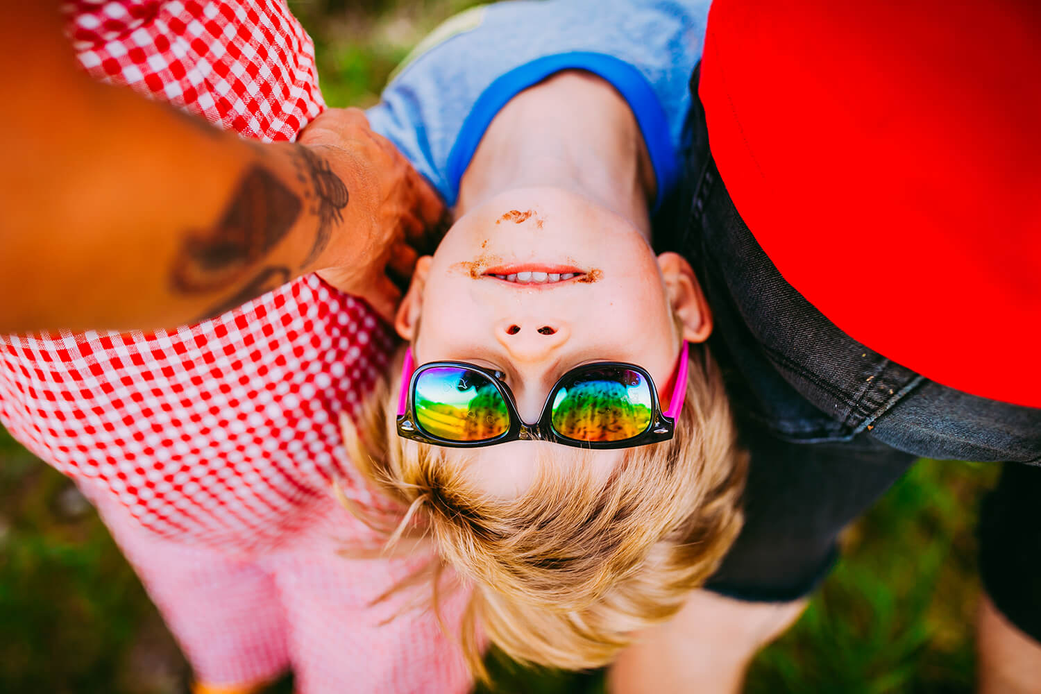 Boy in sunglasses looking at camera upside down