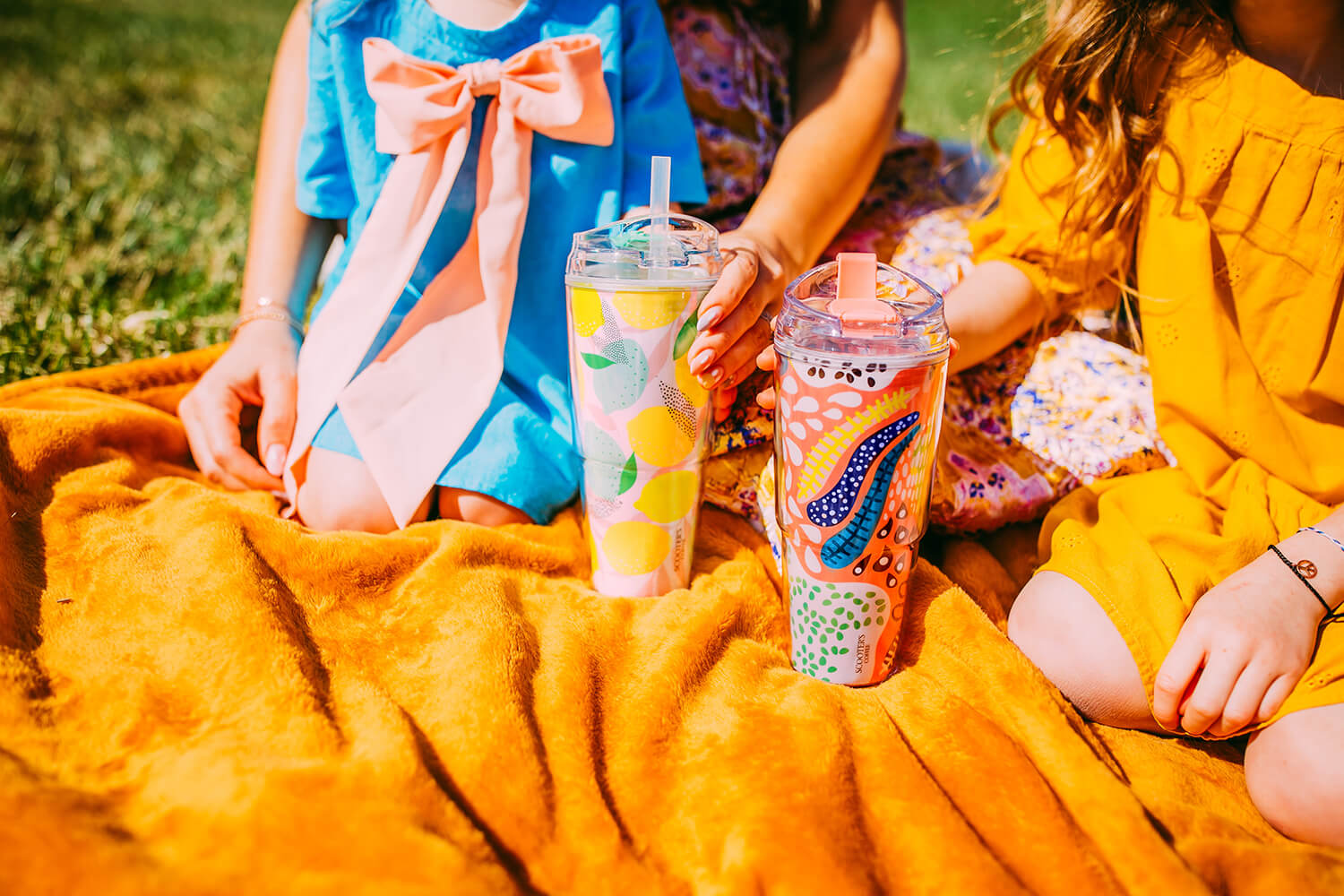 Two colorful cups on picnic blanket