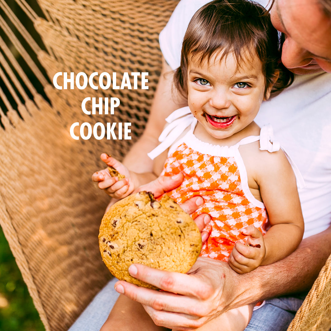 Girl with dad holding chocolate chip cookie