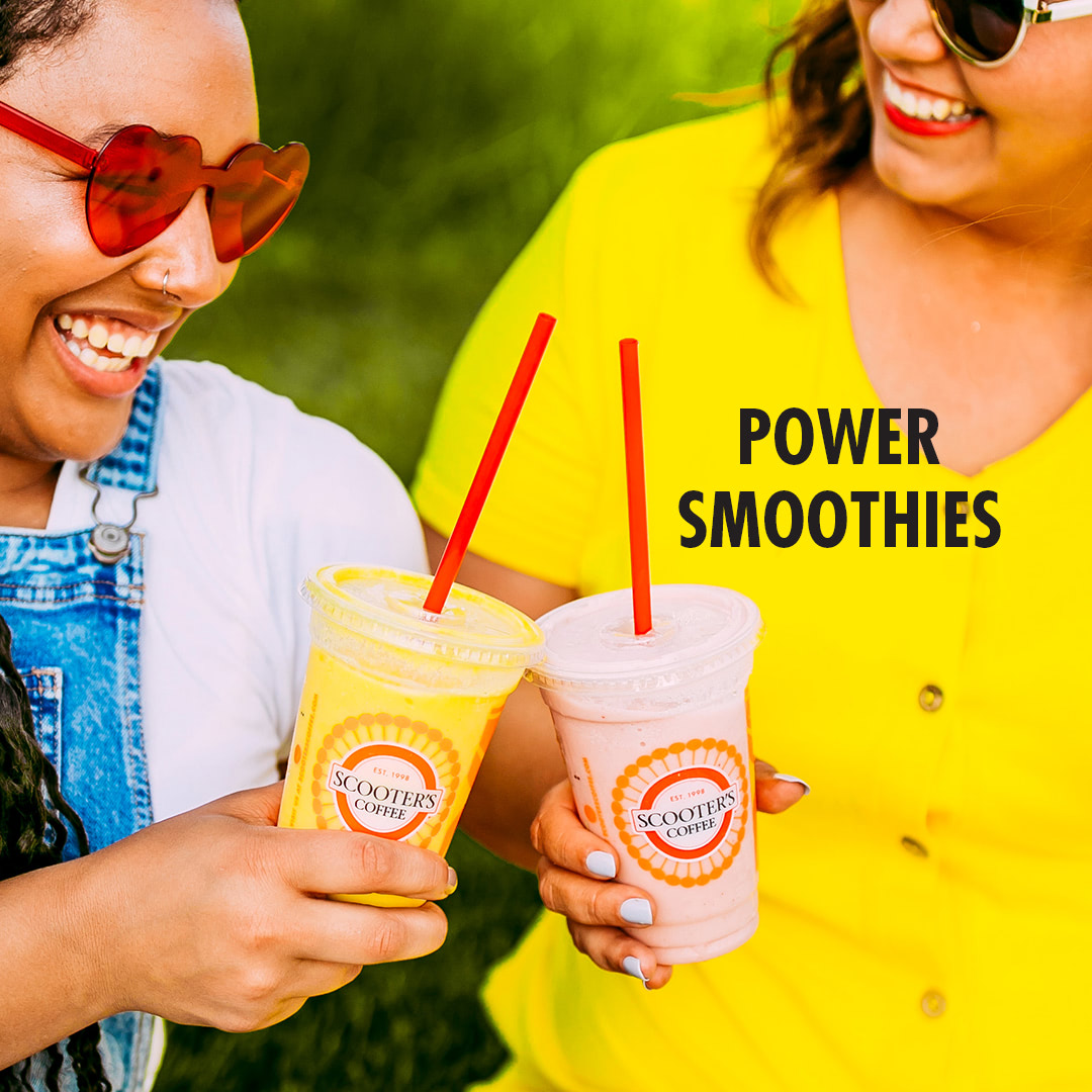 Two women cheers with smoothies