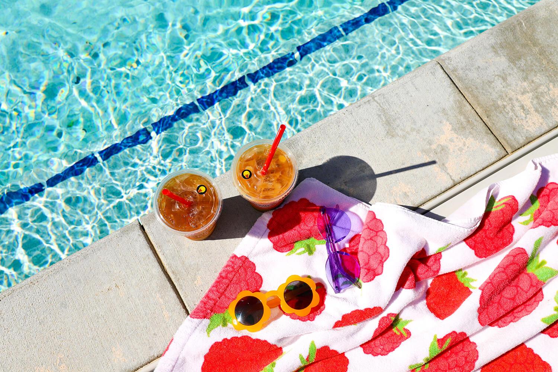 Top down shot of coffee drinks near swimming pool