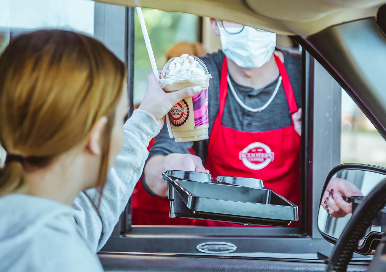 Customer receiving coffee in drive-thru